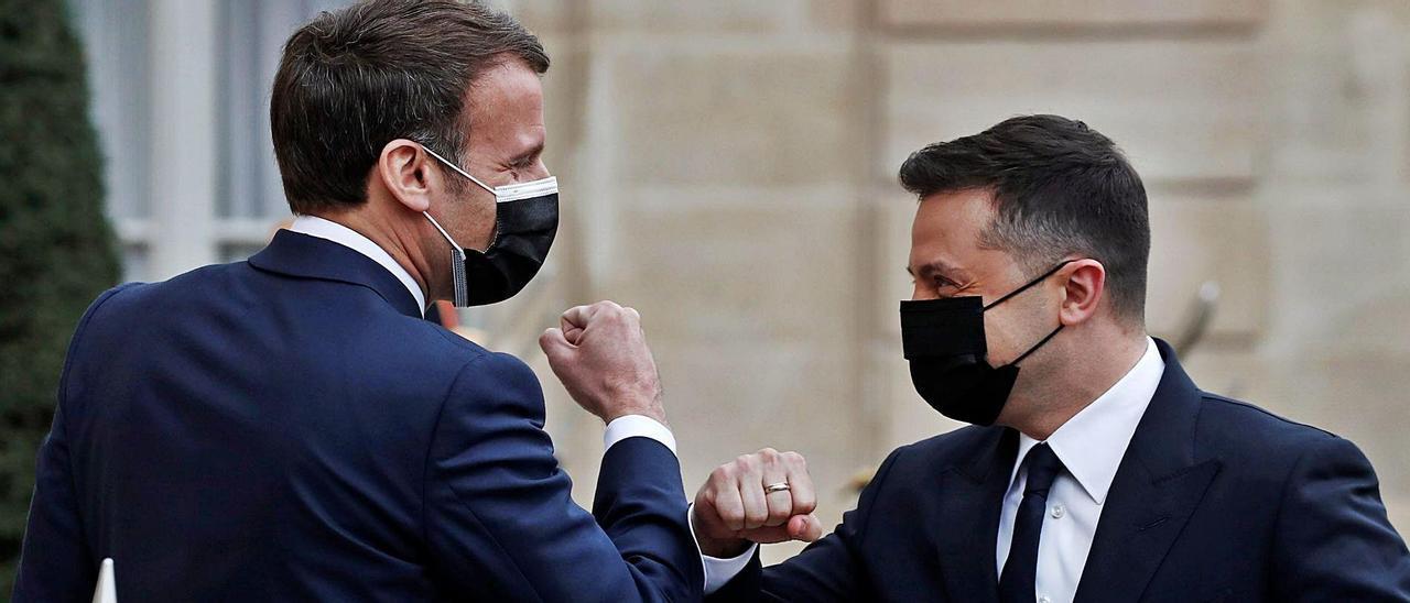 El presidente francés (izda), cuyo país  atraviesa el peor momento de la pandemia, saluda con el codo al presidente de Ucrania. | REUTERS/ BENOIT TESSIER