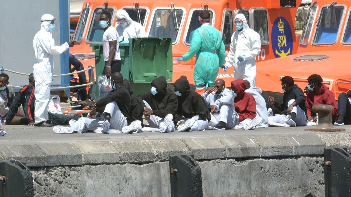 Miembros de Salvamento Marítimo atienden a migrantes llegados al puerto de Los Cristianos, en Tenerife.