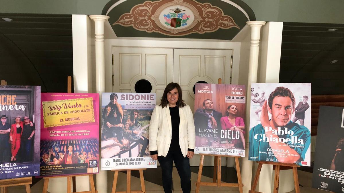 La edil Mar Ezcurra en el Teatro Circo de Orihuela con los carteles de la programación prevista.