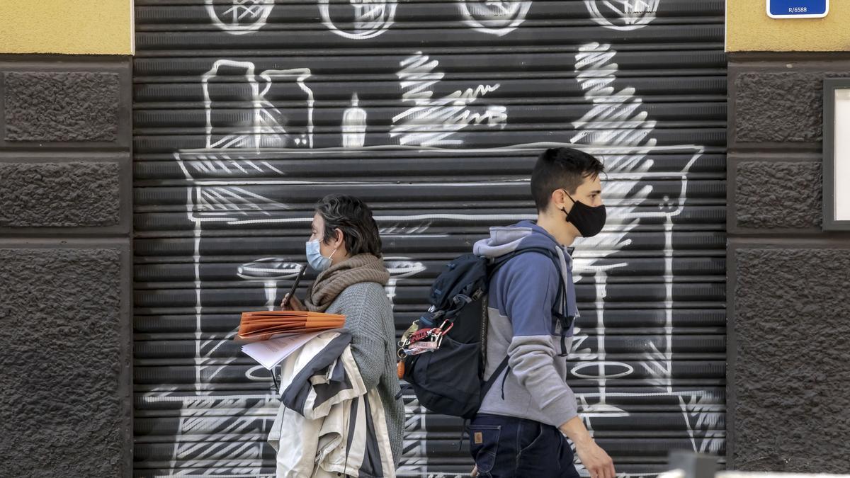 Dos ciudadanos con mascarilla en las calles de Palma