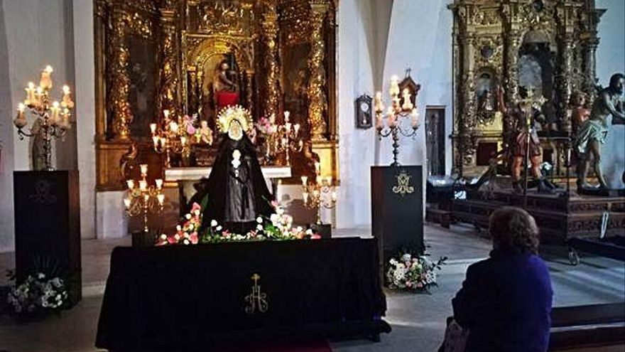 Una mujer contempla la imagen de la Virgen de la Soledad.