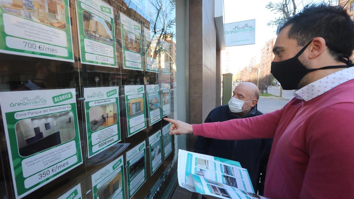 Un trabajador de la inmobiliaria Vivendi enseña las ofertas de viviendas a un cliente, en una imagen de archivo.
