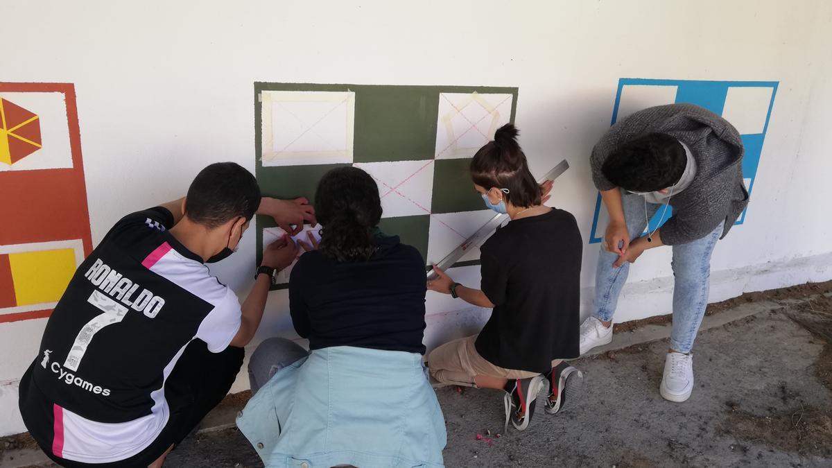 Los estudiantes pintando el bingo de fracciones en las paredes del recreo.
