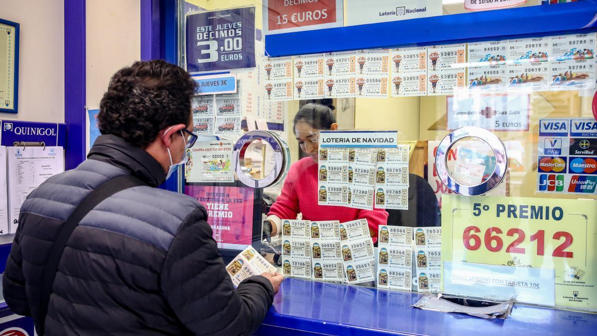 Archivo - Una persona compra un décimo para el Sorteo Extraordinario de la Lotería de Navidad en una administración de Madrid