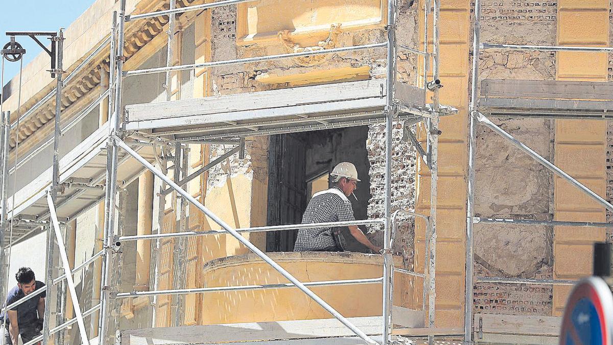 Dos trabajadores arreglan la fachada de un edificio de la ciudad de Cartagena.