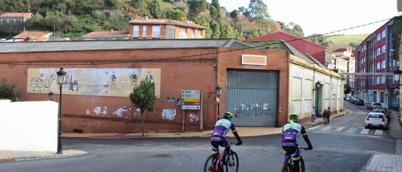 Dos ciclistas, circulando por el entorno de la desaparecida conservera ayer en Candás.