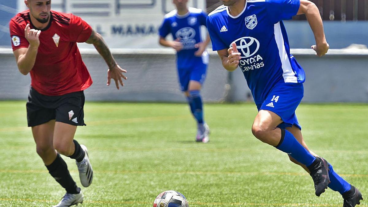 Pedro, jugador del San Fernando, conduce el balón perseguido por un rival del Mensajero durante el choque de ayer. | | ANDRÉS CRUZ