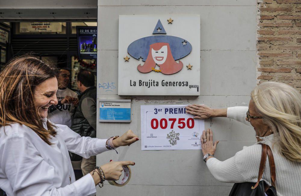 Dos loteras de la administración de la Avenida del Puerto, 173 en Valencia, colocan un cartel con el número 00750, premiado con el tercer premio del Sorteo Extraordinario de la Lotería de Navidad.