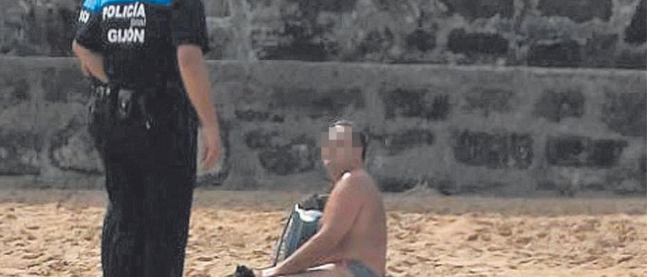 Una pareja de agentes, en San Lorenzo, multando al bañista.
