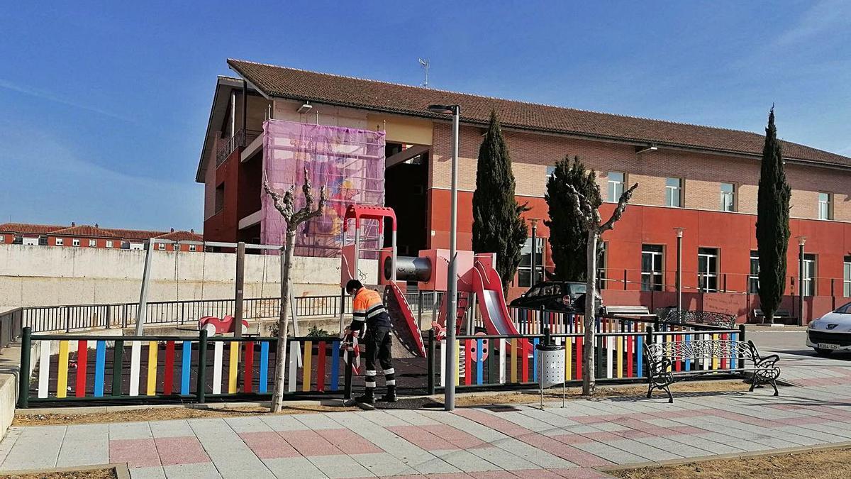 Un voluntario de Protección Civil retira el precinto del parque infantil de la plaza Barón de Covadonga. | M. J. C.
