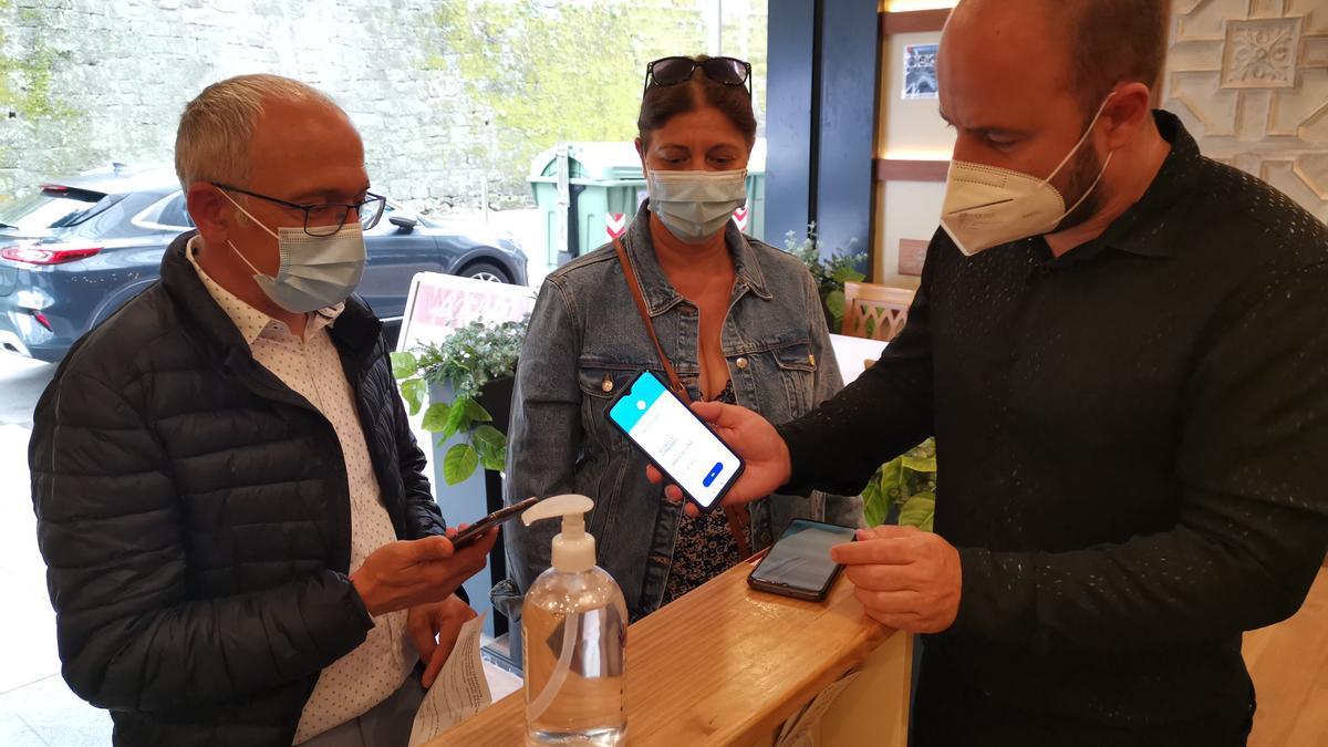 Una pareja muestra sus certificados COVID en sus móviles.