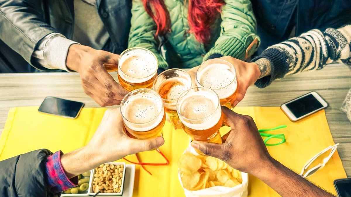 Un grupo de amigos toma unas cervezas en una fiesta.