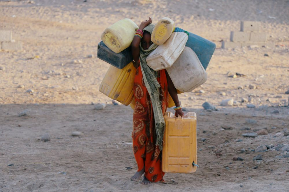 Girl carries jerry cans to fill them up with ...