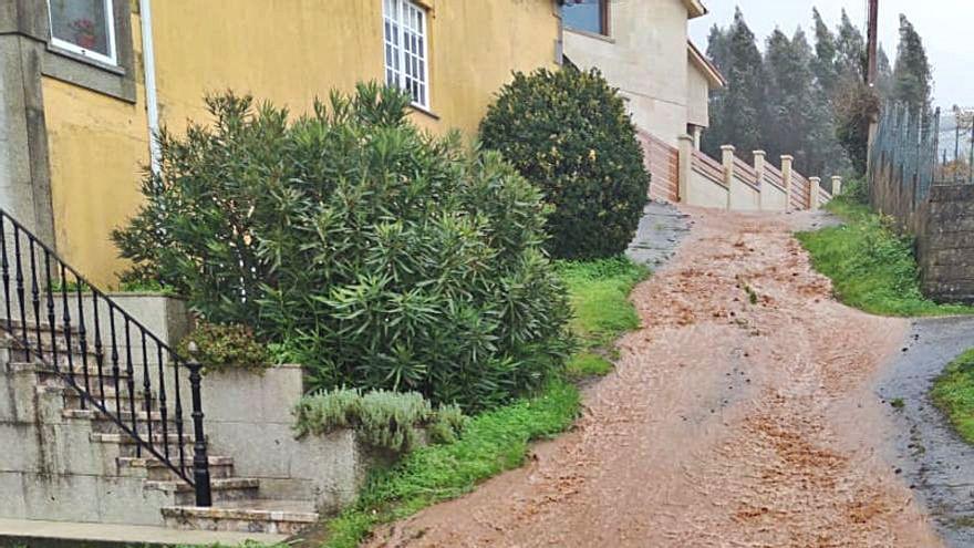 Un río de barro inunda un vial de Guillán, el lavadero y la fuente