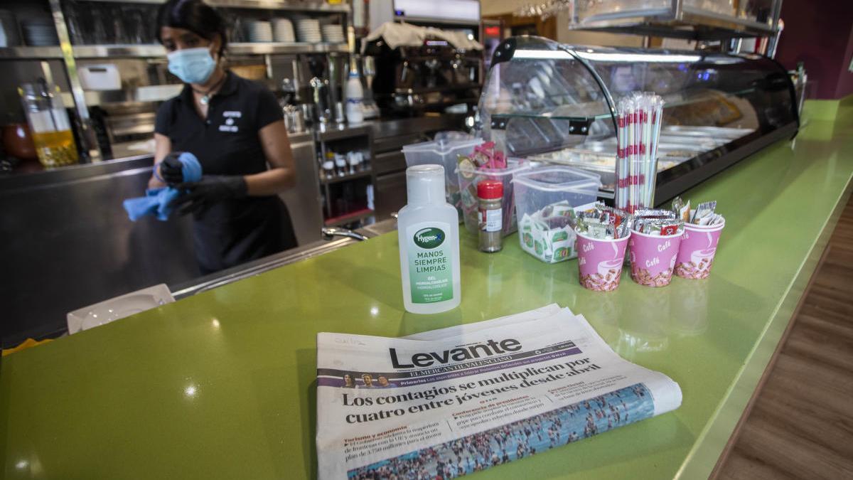 Un ejemplar de Levante-EMV junto a un bote de gel en un bar de València.