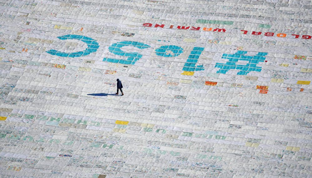 A person walks over 100,000 postcards with ...