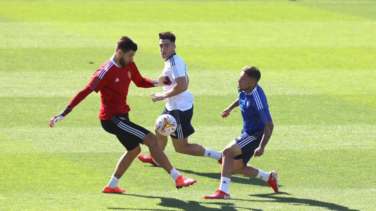 Ratón sale ante Carbonell con Larra siguiendo la jugada en un entrenamiento.