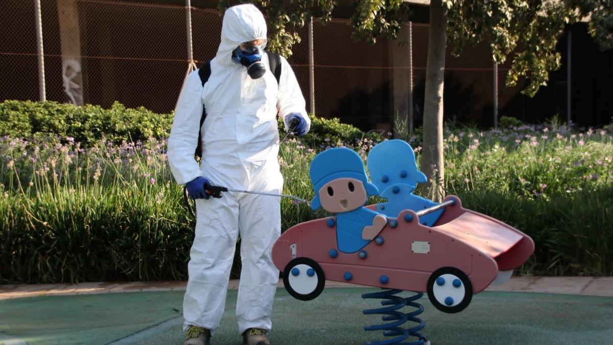 Un operario desinfecta un juego infantil.