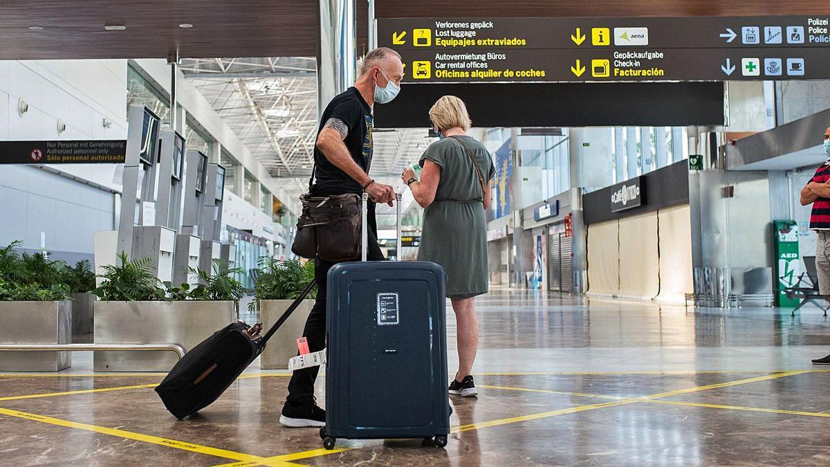 Una pareja de turistas extranjeros se prepara para presentar la prueba PCR negativa a su llegada al aeropuerto de Tenerife Sur.
