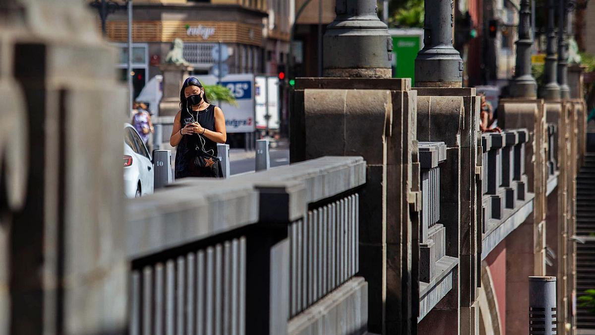 Una joven camina mirando al móvil ayer por el puente Serrador.
