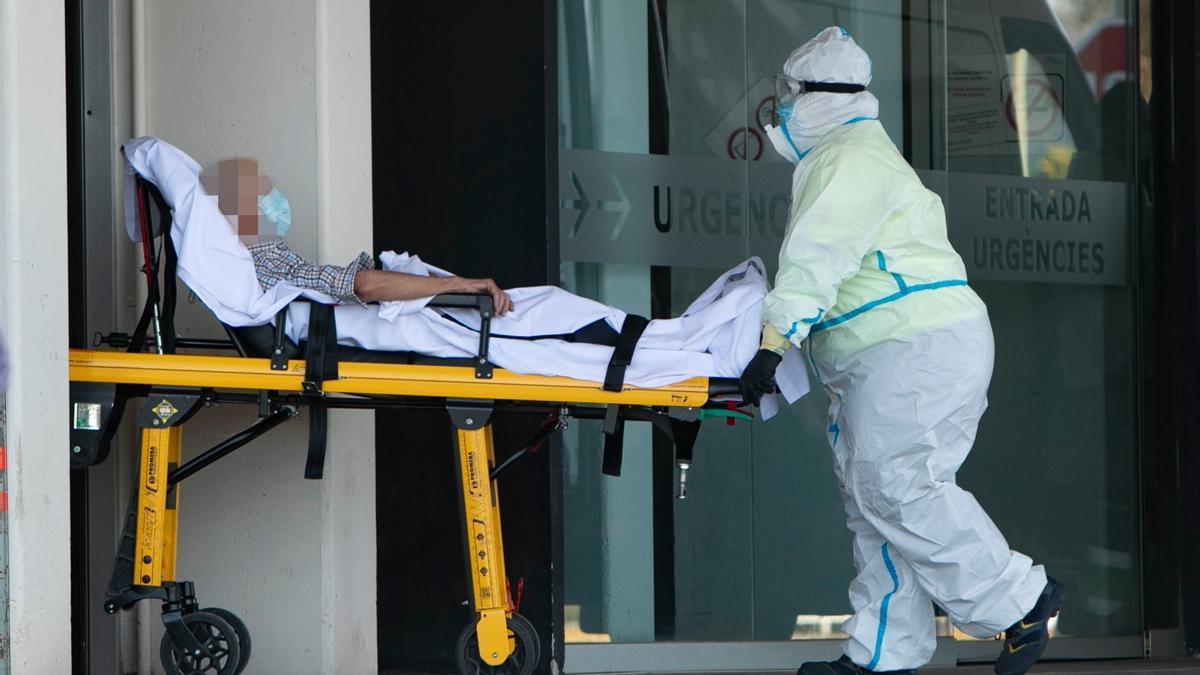Un sanitario traslada a un paciente protegido con un EPI en el Hospital de Sagunt.
