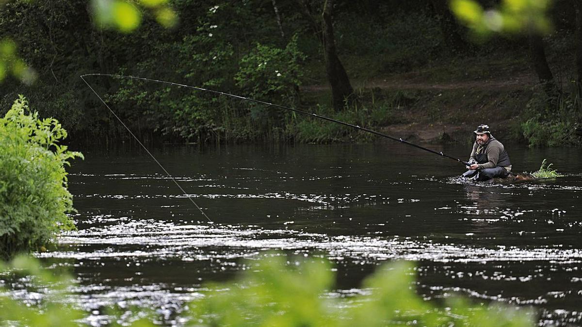 Uno de los participantes prueba suerte sentado en una piedra en el río.   | // BERNABÉ/JAVIER LALÍN