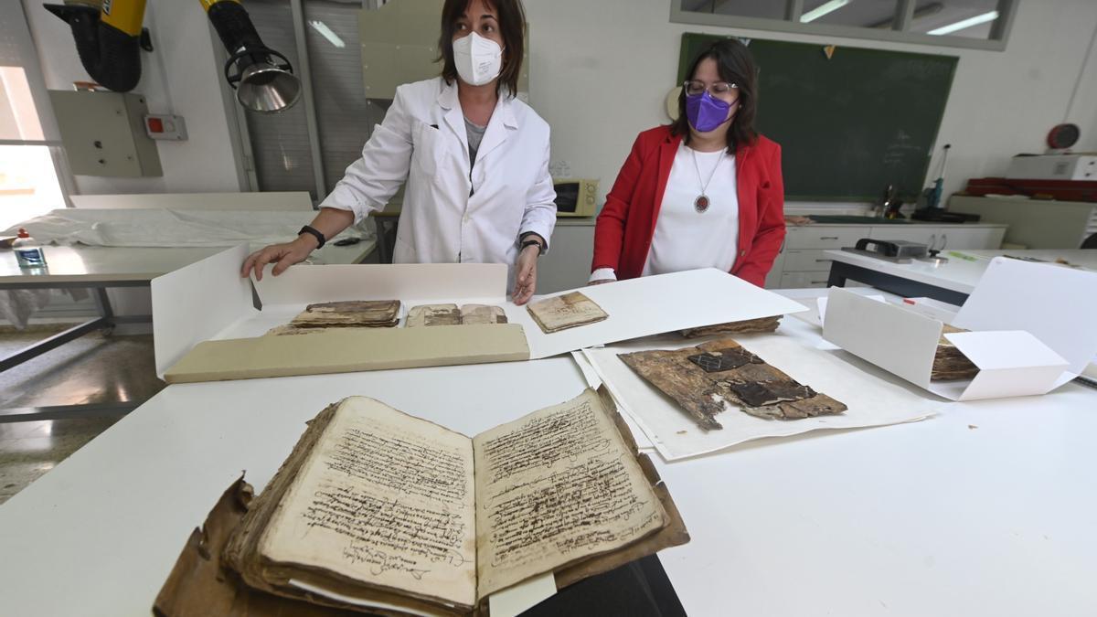 La técnico de restauración de documentación gráfica, Mónica Pintado, junto a la diputada de Cultura de Castelón, Ruth Sanz, observando documentos antiguos del archivo de Zucaina.
