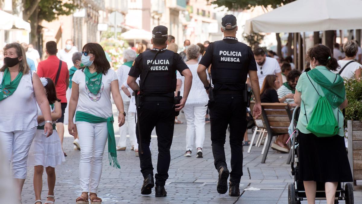 Varias personas caminan por una calle en Huesca.