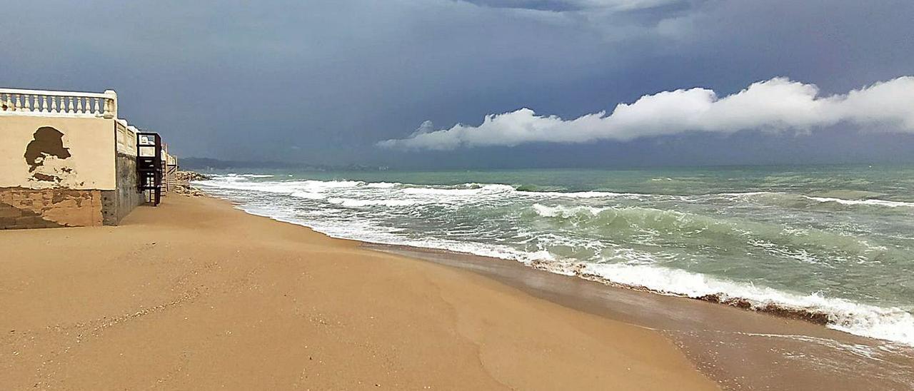 A la izquierda, la playa de la Goleta de Tavernes, sin arena, en el punto donde Costas retiró piedras. A la derecha, un coche trata de atravesar una calle anegada. | T.Á.C. / LEVANTE-EMV