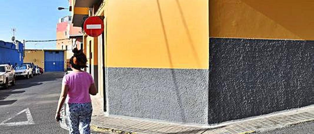 Una vecina camina por el barrio de La Viña, junto a la calle Caridad.