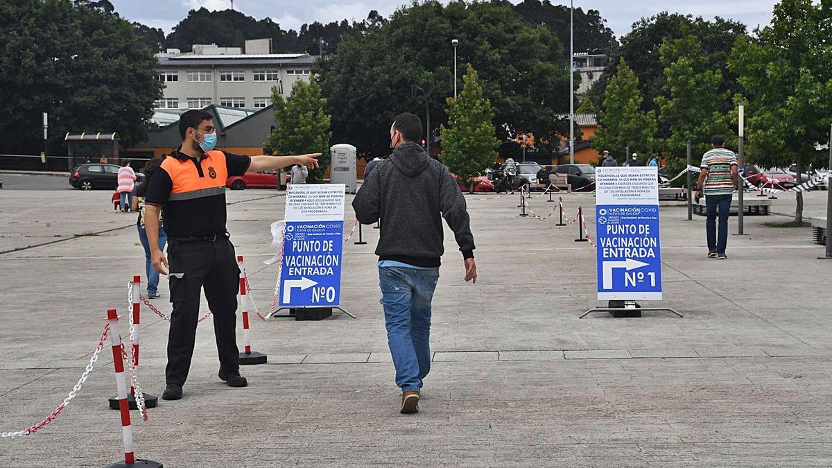 Un voluntario de Protección Civil indica a un usuario su puerta de vacunación en Expocoruña.     // C. P.
