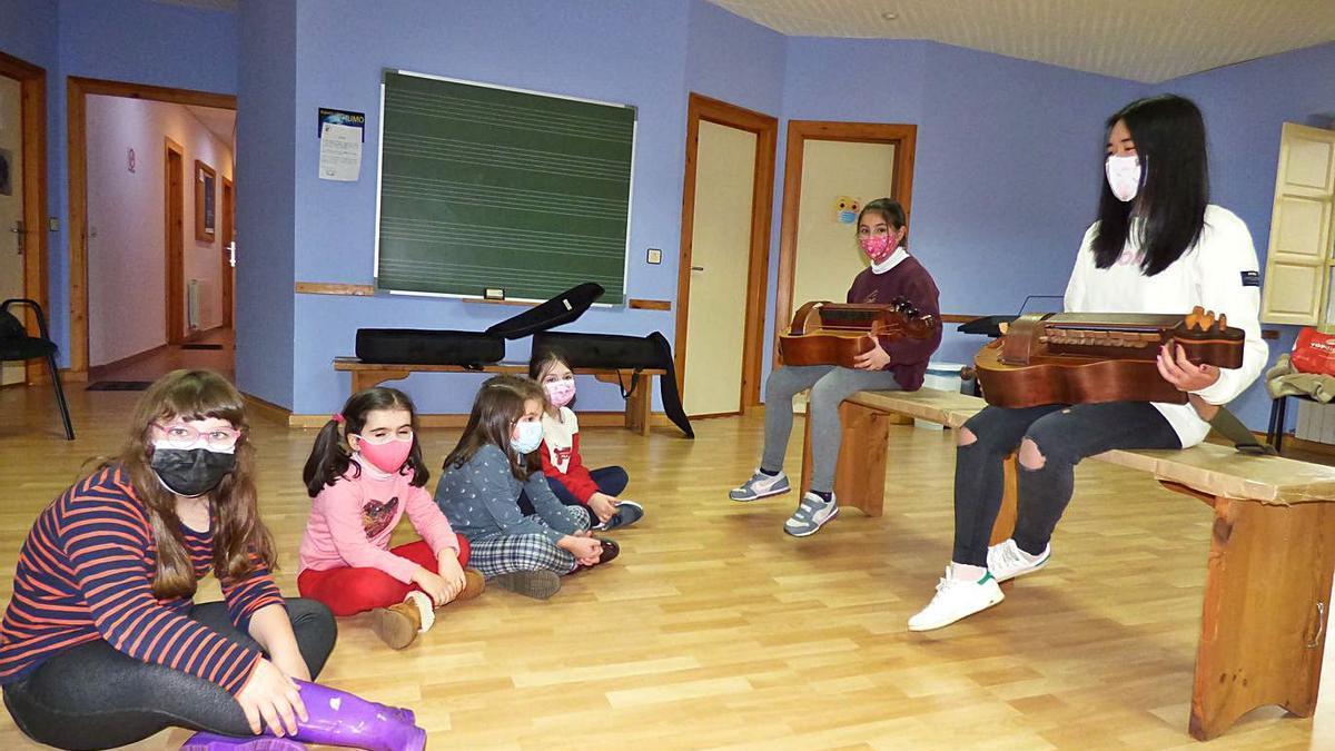 Adriana Vega y Sara Montero muestran las zanfonas a sus compañeras de la Escuela de Música de Tineo Luján Riesgo, Coral Velasco, Alba Fernández y Paula Mayo (de izquierda a derecha). | D. Á.