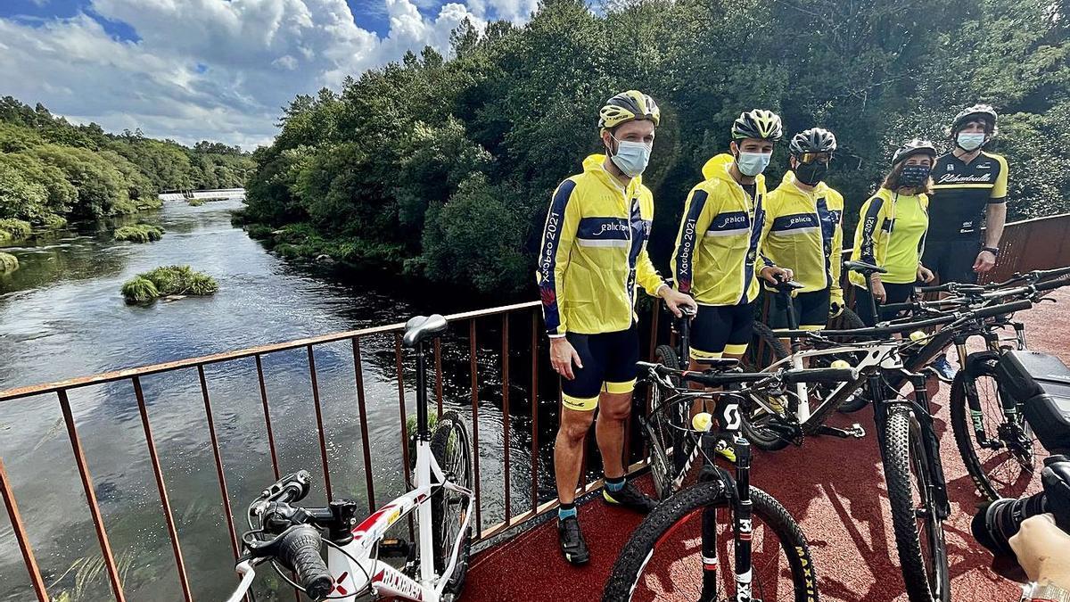Ángeles Vázquez y un grupo de ciclistas, ayer, en el puente de Ximonde, que une A Estrada con Vedra.