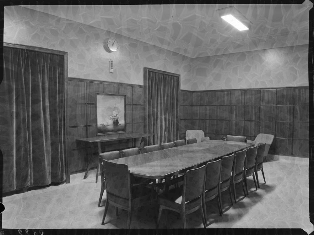 Sala de reuniones con gran mesa central de madera y ventanas tapadas con amplios ventanales.jpg