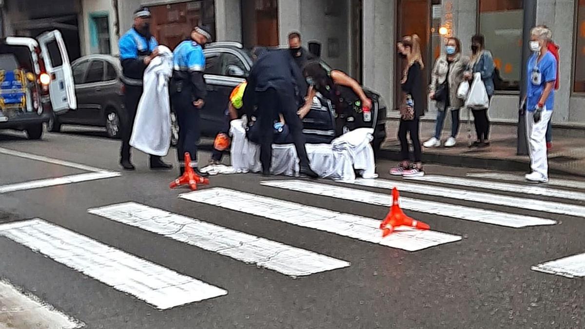 Policía Local y sanitarios auxilian a la mujer, tras el atropello en la calle Ramón y Cajal de Mieres.