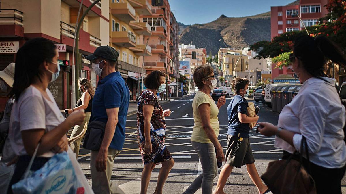 Un grupo de personas se cruzan en un paso de peatones de la capital tinerfeña.