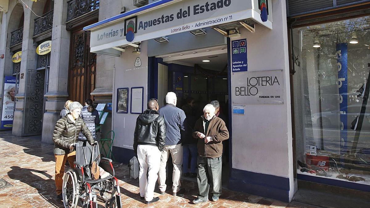 Varias personas son atendidas en una administración de lotería de València.