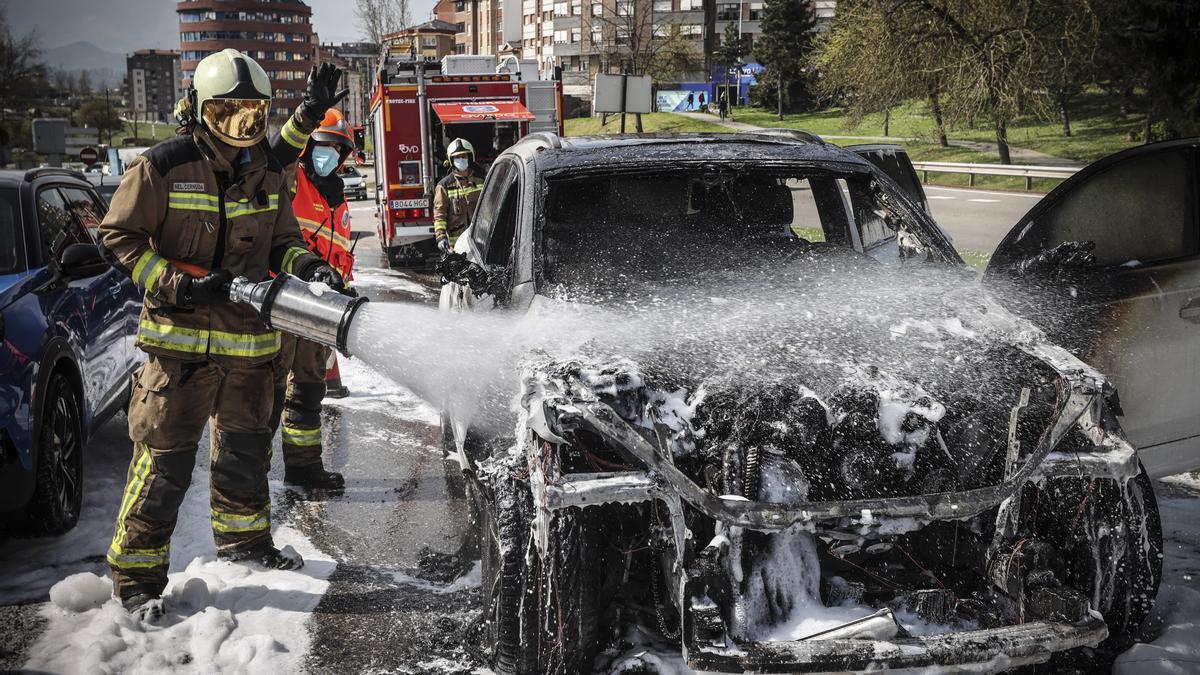 Bomberos, apagando el fuego en un coche en Oviedo