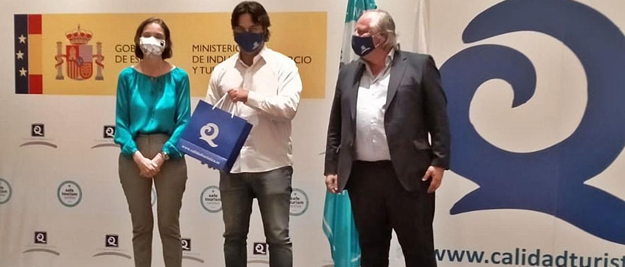 Por la izquierda, Reyes Maroto, Enrique Riestra y Miguel Mirones, en la entrega del distintivo.