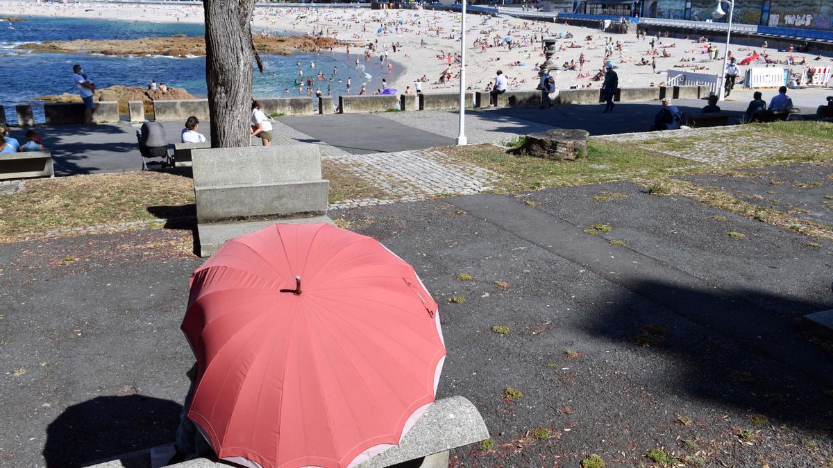 Una persona se protege del sol junto a la playa coruñesa de Riazor.