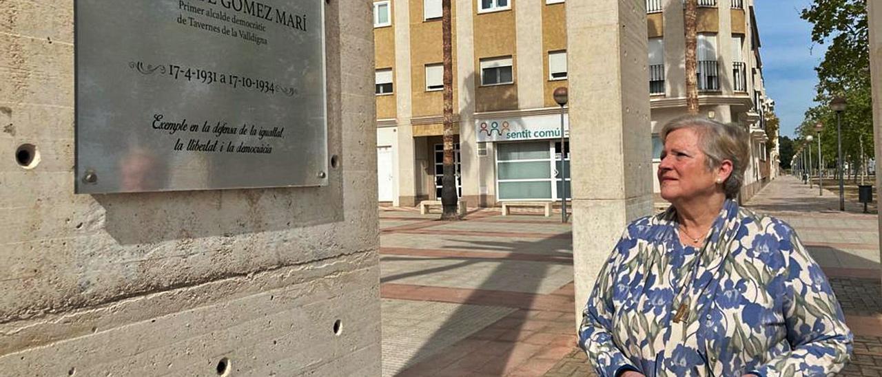 Carmen Gómez mira, ayer, la placa en honor a su abuelo, Vicente Gómez, en la plaza de Tavernes que lleva su nombre. | T. Á. C.