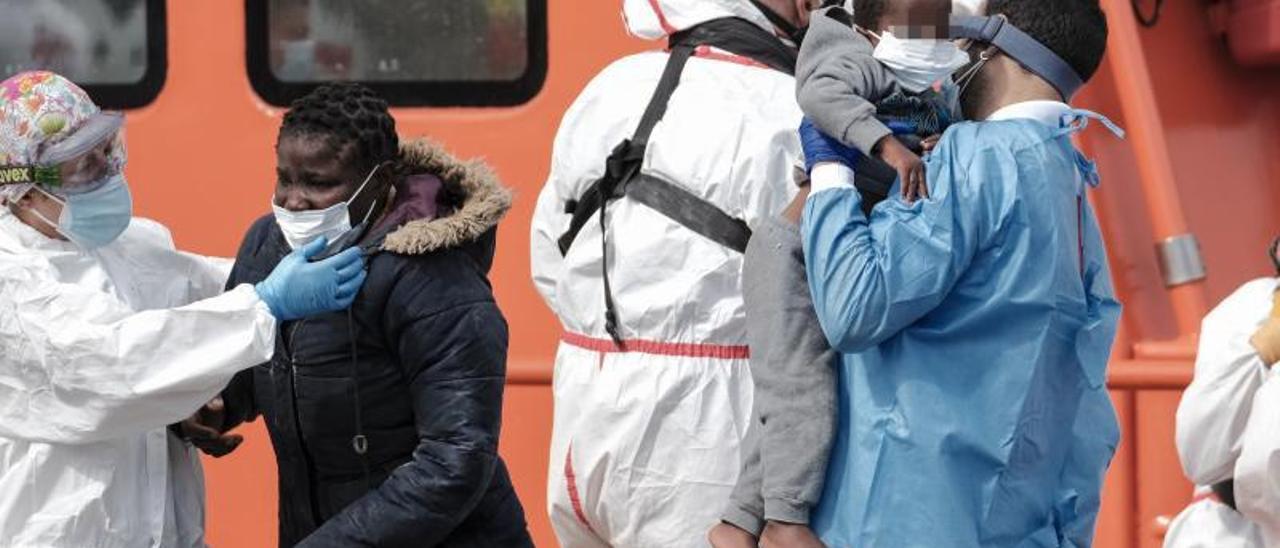 Una mujer y un menor migrante son atendidos a su llegada al muelle de Arguinenín | | EFE / ÁNGEL MEDINA