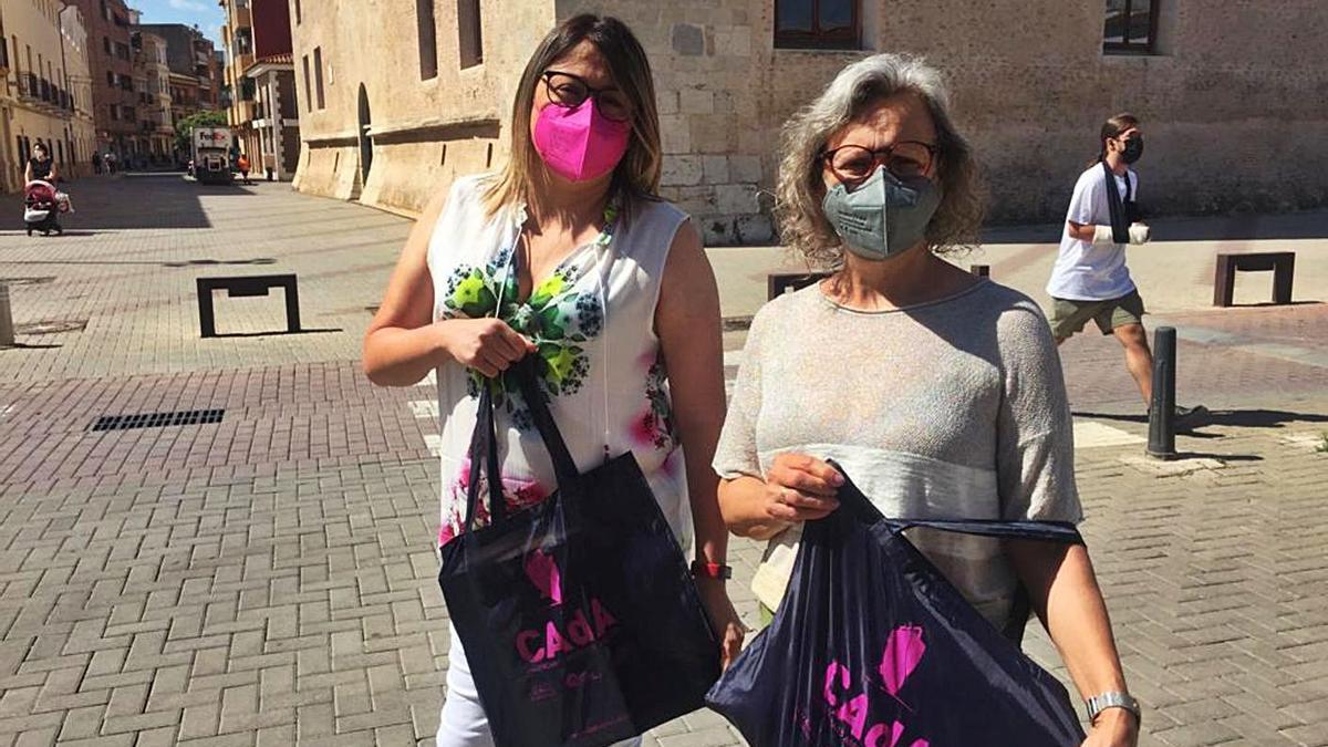 Susana García y Flori Martínez, con las nuevas bolsas reutilizables de CAdA, junto al Castell. | L.SENA