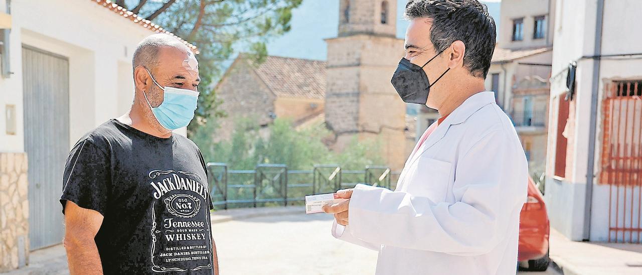 José Ramón García(derecha) da  un fármaco a un vecino de Casas  Altas.