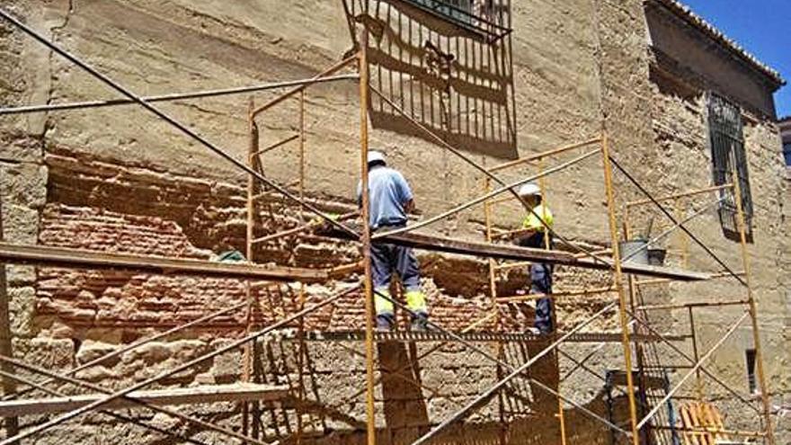 Operarios del servicio de Obras trabajan en la rehabilitación de los muros de tapial de la iglesia.