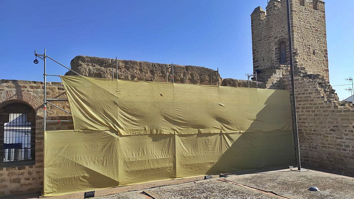 Una lona cubre el espacio de la muralla sometido a restauración.