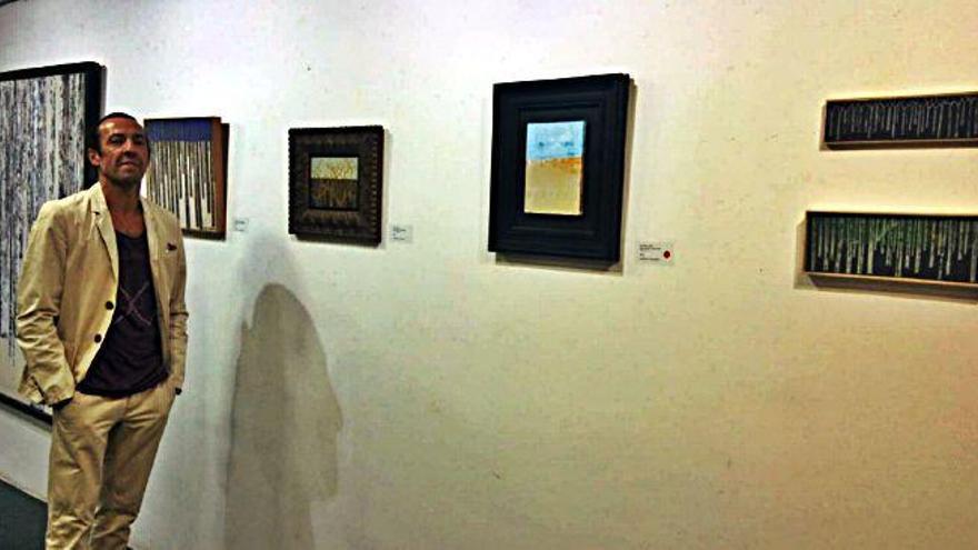 El artista Antonio Vázquez posa junto a varios de sus trabajos expuestos en el estudio charro.