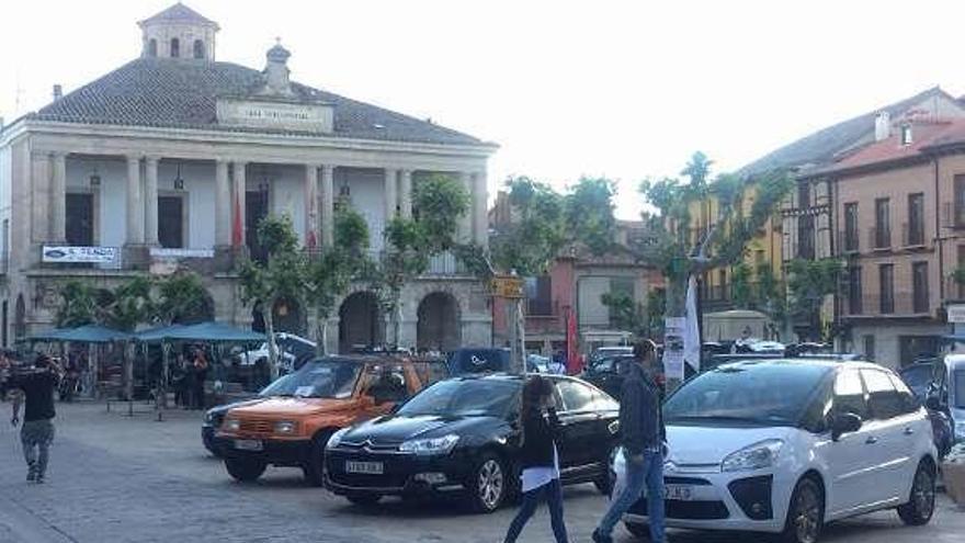 Varios viandantes circulan entre los coches expuestos.