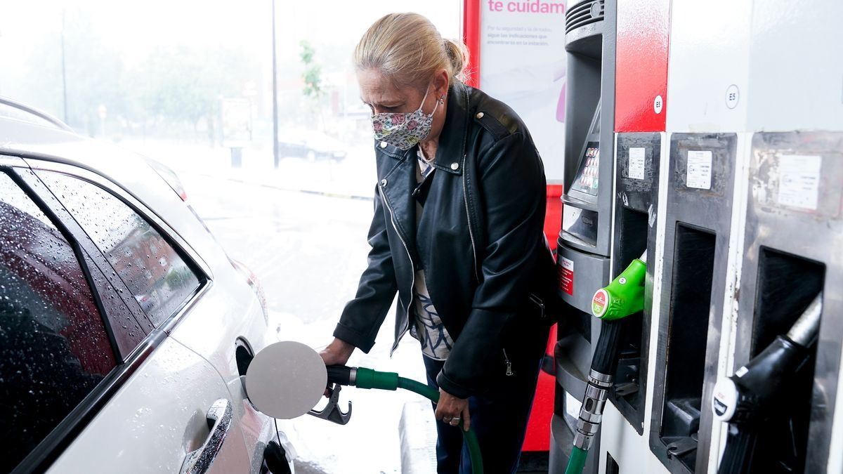 Una mujer pone gasolina a su vehículo en una gasolinera.