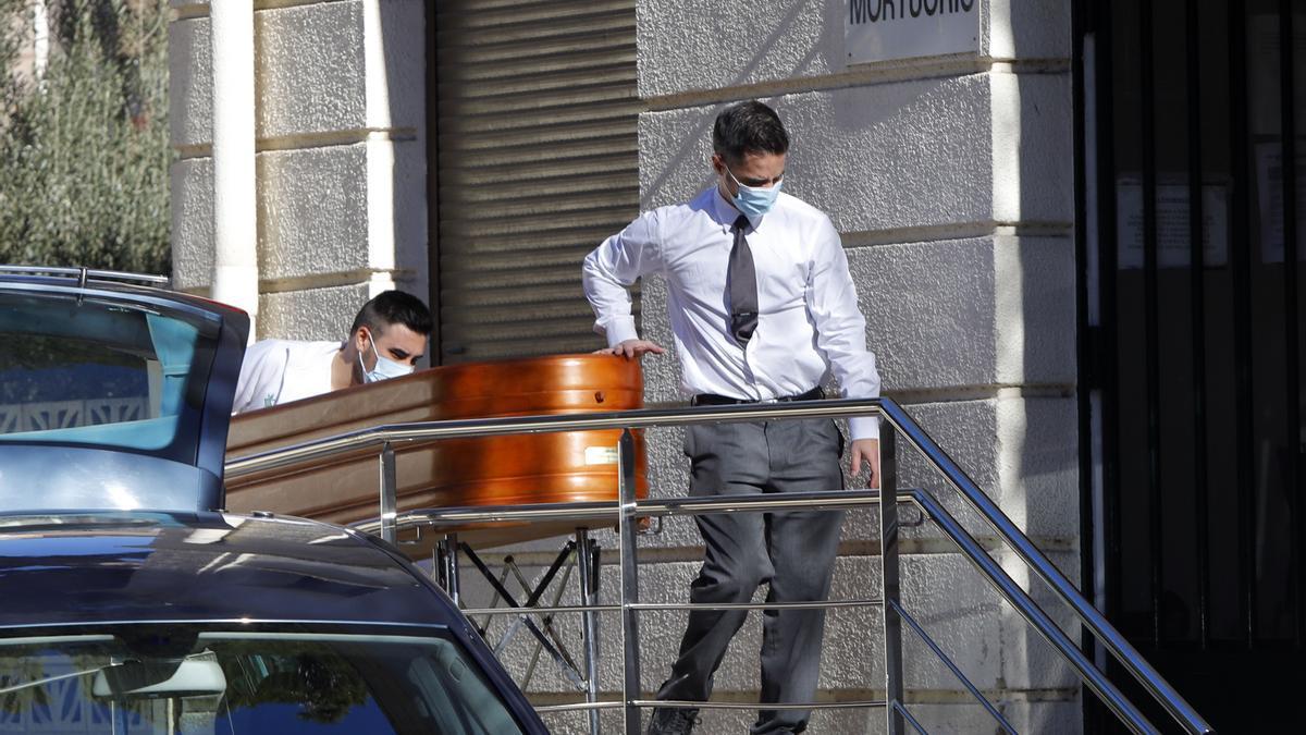 Dos operarios trasladan a un fallecido a la morgue del Hospital General de València.